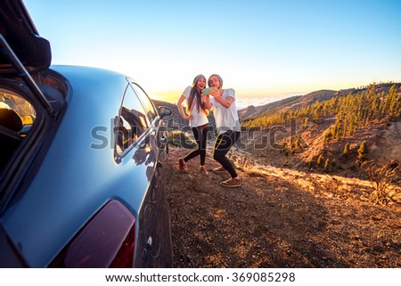 Young couple dressed alike in white t-shirt and hat having fun photographing one another with smart phone near the car on the roadside. Wide angle photo with copy space - stock photo