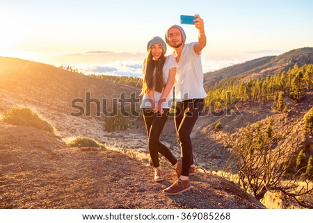 Young couple dressed alike in white t-shirt and hat taking selfie photo with smart phone on beautiful landscape above the clouds