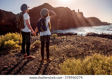 Young couple dressed alike with backpacks traveling island near the rocky ocean coast with lighthouse on the sunset - stock photo