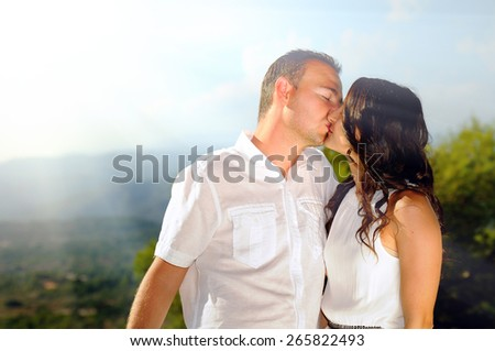 Young couple dressed in white affectionately kissing in the mountains a sunny day
