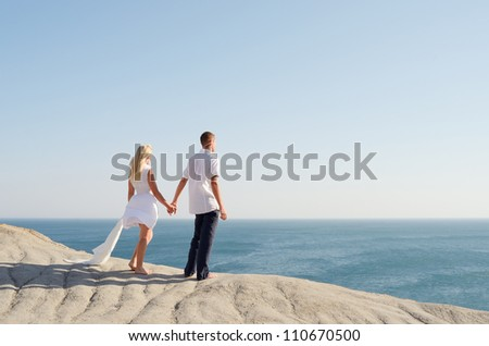 Young couple dressed in white, holding hands and looking at the sea - stock photo