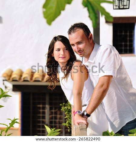 Young couple dressed in white love caught in the railing of a balcony in a cottage - stock photo