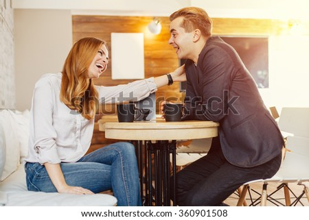 Young couple drinking coffee and laughing in cafe. Selective focus on woman face. - stock photo