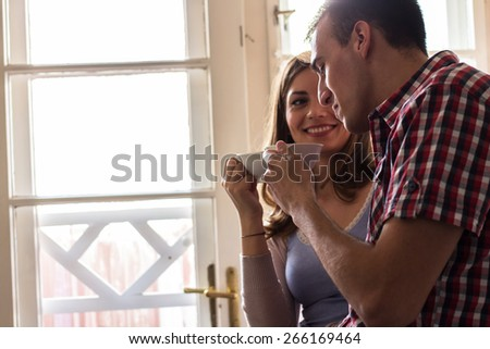 Young couple drinking coffee at the kitchen.Blur and grain added for artistic impression. - stock photo