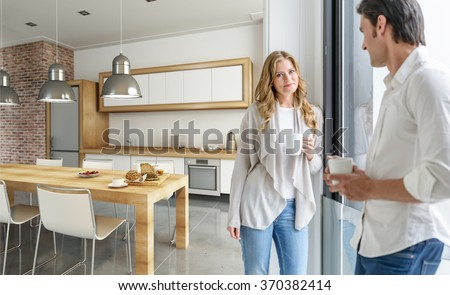 Young couple drinking coffee in a modern kitchen - stock photo