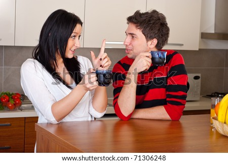 Young couple drinking coffee in the morning and having conversation in their kitchen - stock photo