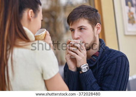 Young couple drinking coffee outside the cafe. - stock photo