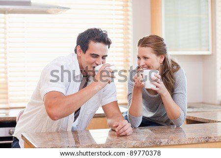 Young couple drinking in the kitchen - stock photo