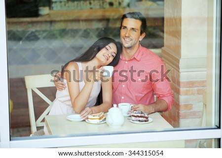 Young couple drinking tea and talking in cafe - stock photo
