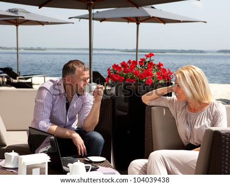 Young couple drinking tea in a cafe on the beach - stock photo