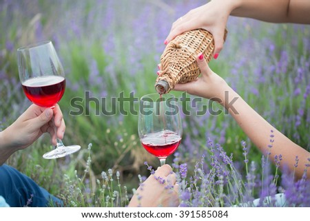 Young couple drinking wine in lavender field