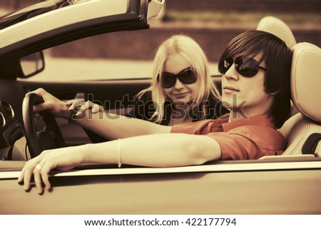 Young couple driving convertible car - stock photo