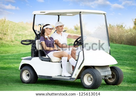 Young couple driving golf cart - stock photo