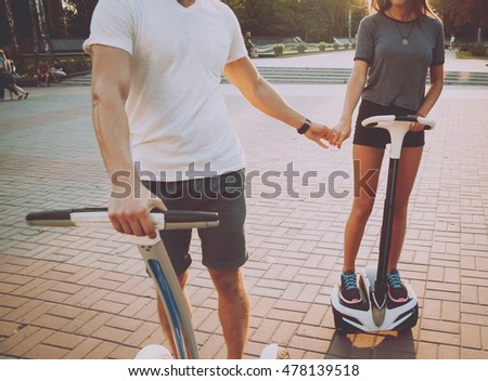Young couple driving on segway in the park.