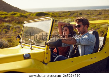 Young couple driving their car on a roadtrip. Handsome young man with his girlfriend on a holiday. Couple on a long drive. - stock photo
