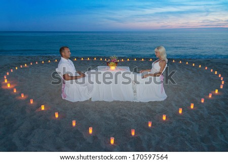 Young couple during romantic dinner with heart of candles on tropical sandy sea beach - stock photo