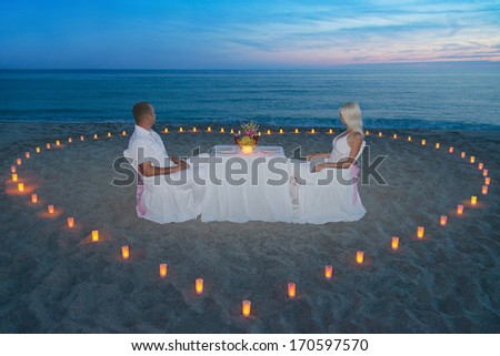Young couple during romantic dinner with heart of candles on tropical sandy sea beach