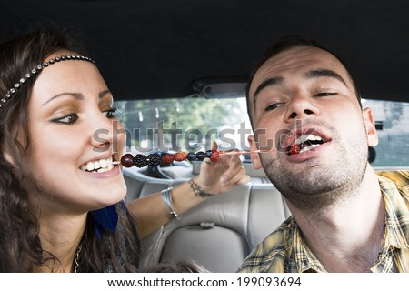 Young couple eating berries in the car - stock photo