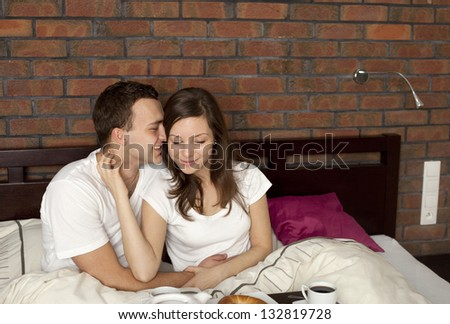 Young couple eating breakfast in the bedroom - stock photo