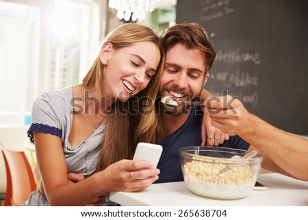 Young Couple Eating Breakfast Whilst Using Mobile Phones - stock photo