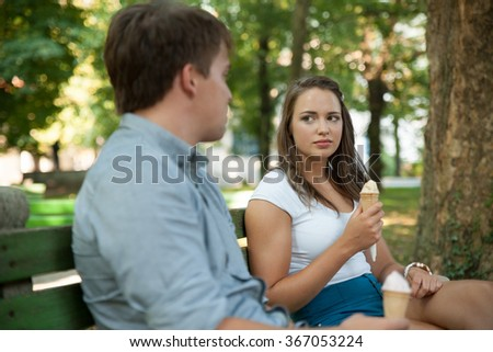 Young couple eating ice cream in shadow on a bench in park on hot summer afternoon - stock photo
