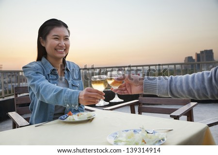 Young couple eating on the roof top, toast - stock photo