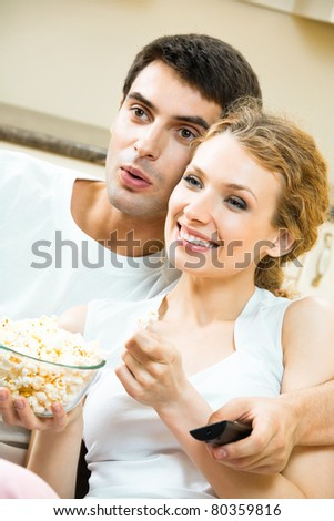 Young couple eating popcorn and watching TV together at home - stock photo