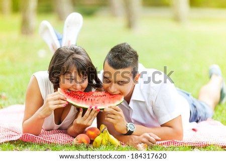 Young couple eating watermelon on a picnic date. - stock photo