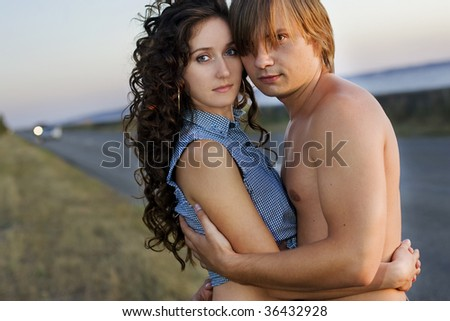 Young couple embrace at the edge of a nice road near the sea.
