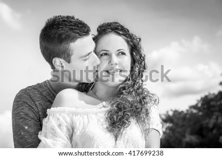 young couple embrace below clouds, while boyfriend kissing his girlfriend - stock photo