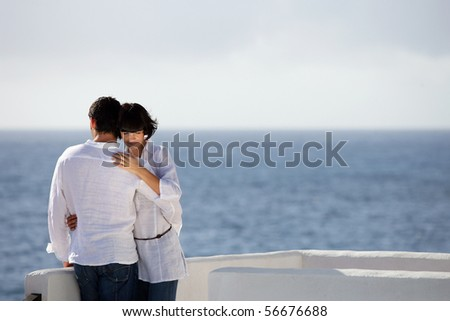 Young couple embraced face to the sea - stock photo