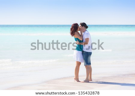 Young Couple Embraced in a Caribbean Beach - stock photo