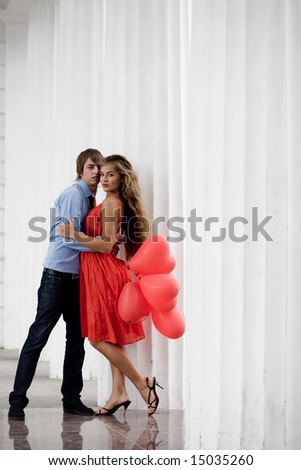 Young couple embracing among white columns and holding bunch of balloons-hearts