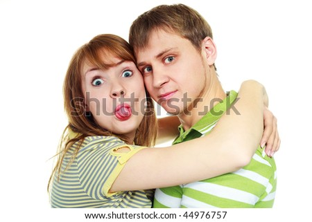young couple embracing and the girl is showing her tongue - stock photo