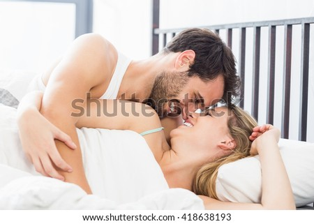 Young couple embracing each other on bed in the bedroom
