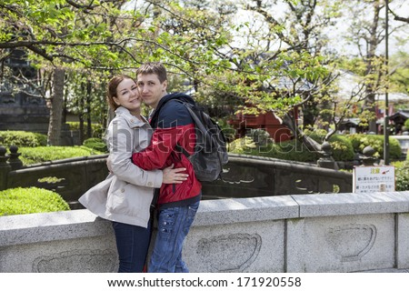 Young couple embracing in the Sensoji shrine garden. Asakusa, Tokyo, Japan