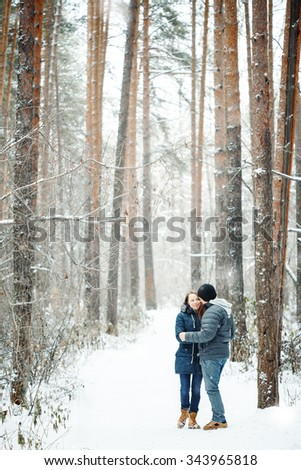 Young Couple Embracing in Winter Forest. Winter Vacations. Weekend Getaway. Space for Text. Natural Colors, Selective Focus. - stock photo