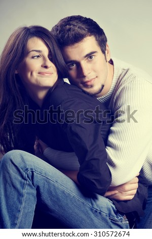 Young couple embracing, looking at camera - stock photo