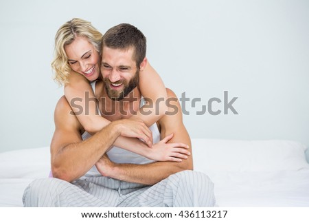 Young couple embracing on bed at bedroom