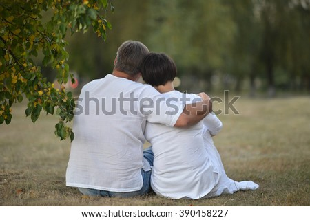 Young couple embracing sitting beside the road