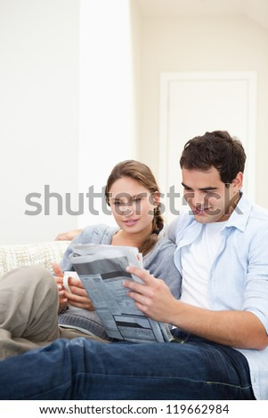 Young Couple embracing while reading a newspaper in a sitting room - stock photo