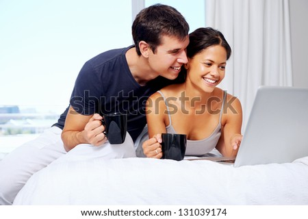 young couple enjoy coffee and relax at home with laptop and love - stock photo