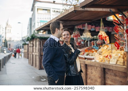 young couple enjoy different kinds of candy  in the street in Seville  - stock photo