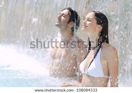 Young couple enjoy together waterfall freshness in a swimmingpool