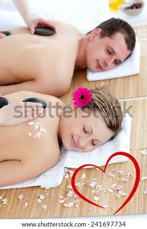 Young couple enjoying a back massage with stone against heart