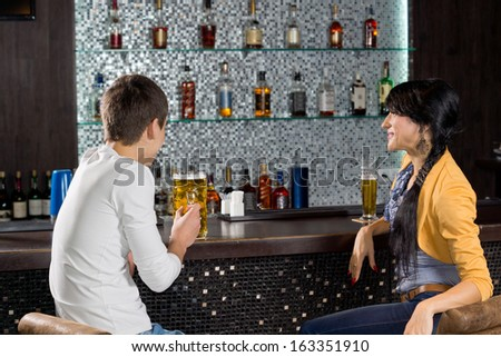 Young couple enjoying a date drinking a beer at the bar sitting at the counter chatting with a display of alcohol bottles on shelves behind them - stock photo