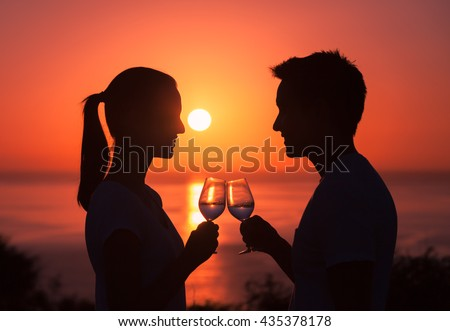Young couple enjoying a glass of wine on the beach. Vacation and holiday concept.  - stock photo