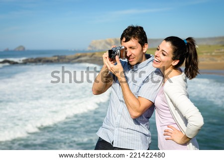 Young couple enjoying coast travel taking photo to the ocean. Man photographing to the sea with retro camera and brunette female smiling.