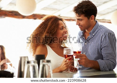 Young Couple Enjoying Drink At Outdoor Bar Smiling