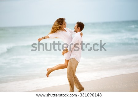 Young couple enjoying each other on a beach. - stock photo